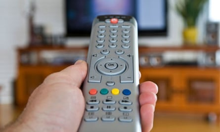 A hand holds a television remote control