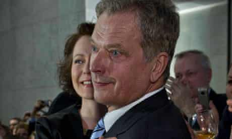 Saul Niinisto is hugged by his wife as early election results are announced in Helsinki