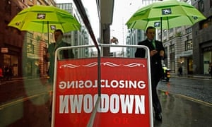 A pedestrian passes a board promoting a closing down sale in the City of London