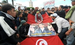 Inhabitants of Kasserine, Tunisia, walk with the Tunisian flag during clashes in January 2011