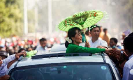 Suu Kyi greets supporters on the campaign trail