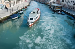 Frozen Venice: a waterbus (vaporetto) sails along a partially frozen canal