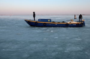Frozen Venice: People stand on a boat on the frozen Lagoon