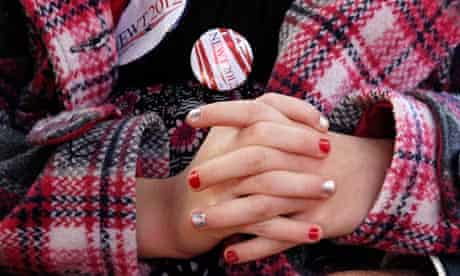 Clasped hands of a young girl listening to Newt Gingrich speak