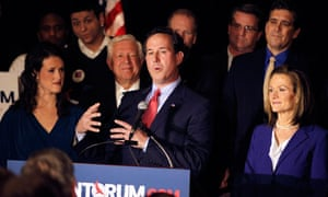 Rick Santorum addresses supporters last night. A smiling Foster Friess stands just behind him.