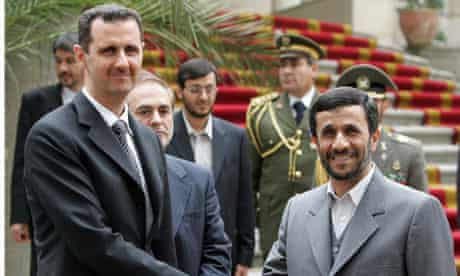 Syrian president Bashar al-Assad shakes hands with his Iranian counterpart