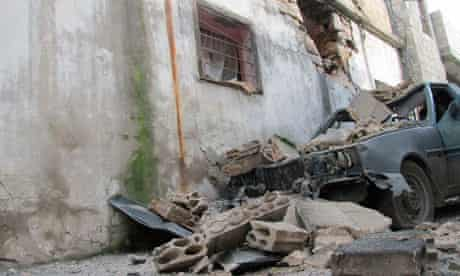 The remains of a wrecked vehicle next to a damaged house in Baba Amr, Homs