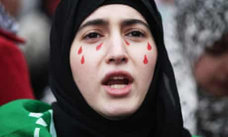 A demonstrator protests in front of the Syrian embassy in London