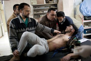 Syria Annan: A Free Syrian Army fighter attended by doctors during fighting