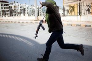 Syria Annan: A Free Syrian Army fighter runs for cover in Idlib, Syria