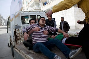 Syria Annan: Injured men are carried to a hospital in Idlib, Syria