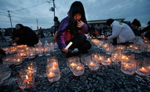 Japan anniversary: A girl lights candles in front of a temporary shopping complex in Kesennuma