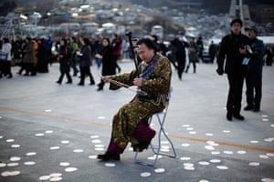 Japan anniversary: A musician performs as local residents prepare to observe moment's silence