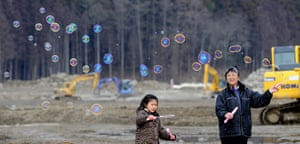 Japan anniversary: Hiroko Oyama and granddaughter play with bubbles as they pray for victims