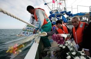 Japan anniversary: Fishermen throw flowers and lanterns into the sea as they offer prayers