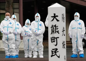 Japan anniversary: Evacuees of Okuma town, dressed in protective suits, offer prayers