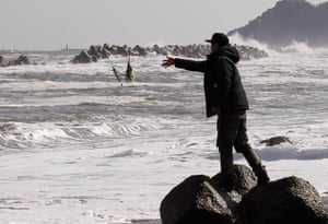 Japan anniversary: A mourner throws flowers into the sea in Iwaki, Fukushima prefecture