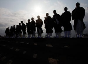 Japan anniversary: Bhuddhist monks form a line on the water's edge