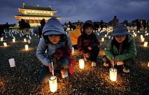Japan tsumani: Children light candles during a memorial service in Nara