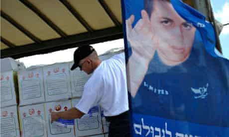 Noam Shalit places a sticker on goods aboard a truck
