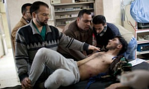 A Free Syrian Army fighter is attended by doctors