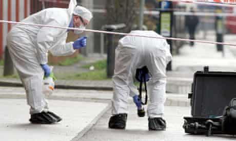 Police forensic experts examine the scene of the Belfast shooting