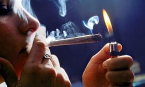 A woman lights a marijuana cigarette