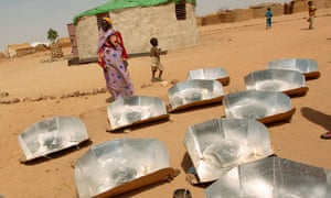 Sudanese refugees stand around solar stoves