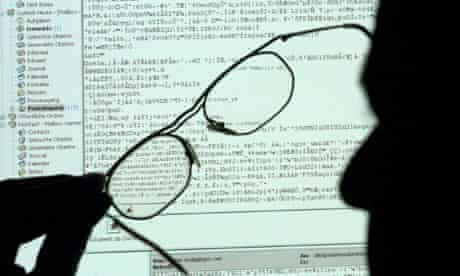 Silhouette of a man in front of a computer screen