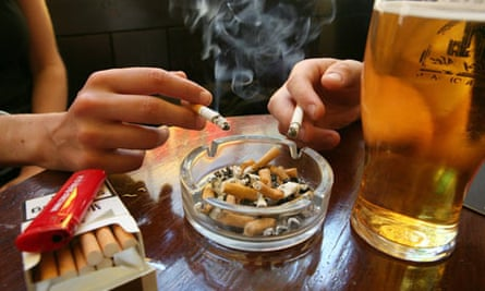 Couple smoking cigarettes in a pub