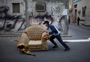 24 hours: Sanabis, Bahrain: An anti-government protester pushes an armchair