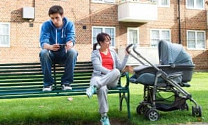 Poor, uncommunicative teenage couple with pram in front of council flats