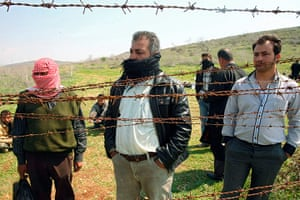 Syrian Refugees: Syrian refugees look through barbed