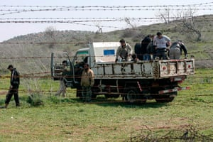 Syrian Refugees: Syrian refugees look on March 27, 2012 through a barbed wire fence