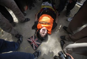 Tibet Protests: A Tibetan exile shouts slogans while lying on the ground during a protest
