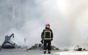 Spain strikes: Barcelona: A fireman looks at several charred rubbish skips