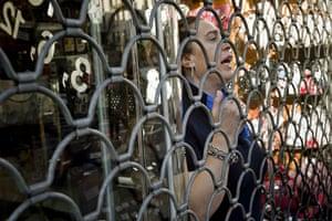 Spain strikes: Madrid: A woman behind a shop's iron gate
