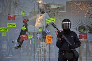 Spain strikes: Pamplona: A riot police officer protects a shopping centre
