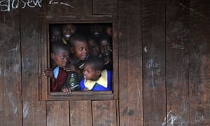 School children look through a window of their school