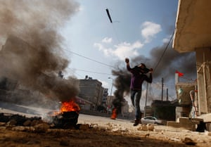 Land Day protests: A Palestinian protester uses a sling to hurl stones near Ramallah