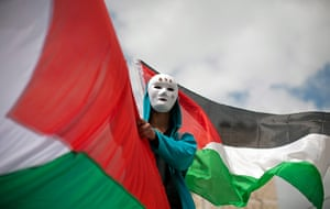 Land Day protests: A Palestinian man waves his national flag during clashes at the Kalandia