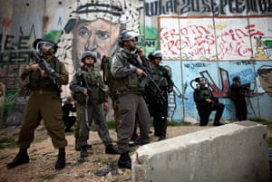 Land Day protests: Israeli border policemen stand under a painting of late Yassir Arafat