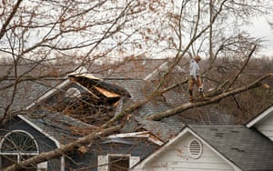 Midwest tornado: A worker stands on a downed tree that rests on a home in Charlotte