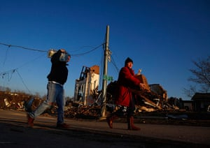 Midwest tornado: People carry supplies past a damaged church in West Liberty, Kentucky