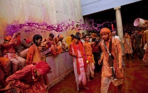 Lathmar Holi : An Indian Hindu worshipper throws a bucket of coloured water on others