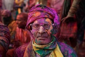 Lathmar Holi : An Indian Hindu worshipper is covered in coloured powder