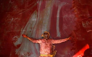 Lathmar Holi : A man daubed in coloured powder lies on the ground as he celebrates