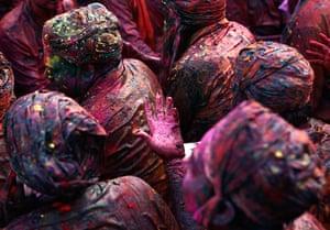 Lathmar Holi : Men daubed in coloured powder sing a hymn at a temple