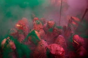 Lathmar Holi : Indian Hindu worshippers pray as others throw coloured powder and water