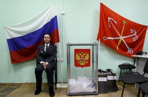Russian election: St.Petersburg: A Russian police officer sits next to a ballot box